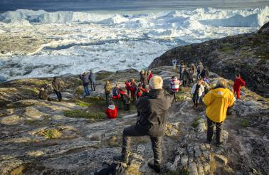 Visitors overlook the Ilulissat Icefjord from Sermermiut